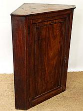 An early 19thC flame mahogany panelled hanging corner cupboard, the door opening to reveal four shelves with and a small