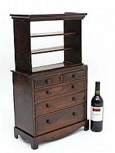 A 19thC miniature bookcase chest, the top with three open shelves with 2 short and 3 graduated long drawers with a bow s