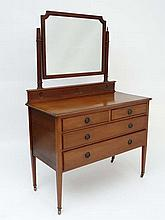 An early 20thC mahogany dressing table having a shaped bevel edged mirror over two short legs and 2 short drawers with s