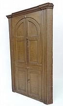 A Victorian pine comb decorated floor standing corner cabinet with 2 pairs of opening doors ( the top of arch form ) wit