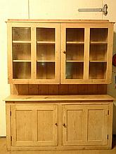 Pine dresser :a Victorian and later pine dresser with twin glazed doors opening before two shelves, an open middle secti