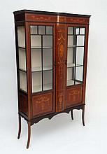 An Edwardian mahogany display case having twin glazed doors before four shelves with swag and bow decoration and hair be