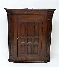A 19thC oak Gothic style corner cupboard with lancet shaped moulded recesses 45 1/2