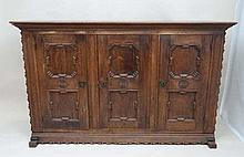 An early 20thC German oak 3 door cupboard with geometric like framed panelling, the doors opening to reveal 2 shelves wi
