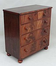 An early - mid 19thC mahogany chest of drawers comprising  2 short over 3 graduated long drawers with short turned feet
