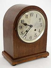Clock : an Oak cased Arch top 8 day striking mantel clock with movement striking on a coiled gong, silvered dial , minut