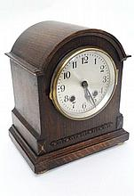 HAC Mantel Clock : a smaller arch topped oak cased bracket shaped clock with silvered dial having minute markers and Ara