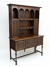 A c.1900 oak dresser with cupboards and open sections to top and 2 doors flanked by 2 cupboard doors to base on turned l
