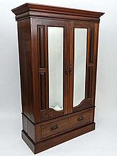 A late Victorian walnut double wardrobe with 2-bevelled mirrors to each door opening above a single drawer under 51