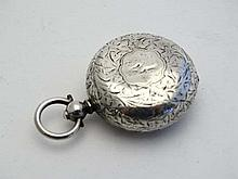 A silver sovereign case of pocket watch form with engraved acanthus decoration. Approx 1  1/8