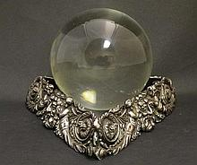 A glass / crystal ball of spherical form with a silver plate stand of triangle form with acanthus scroll, cherub and gre