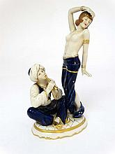 A Royal Dux Art Deco figure group depicting a half naked female in exotic dance pose while a turbaned flute player sits