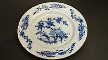An 18thC Delft plate painted in blue with Chinoiserie floral design with trailing foliate sprays to border. Diameter 9