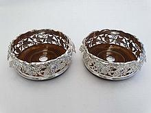 A pair of silver plate decanter/ bottle coasters with ornate cast fruiting vine decoration and turned wooden bases. Appr