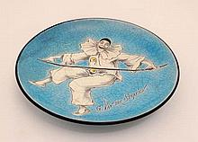 An early 20thC enamelled decorative dish depicting Pierrot holding a balancing stick on a crackle glazed turquoise groun