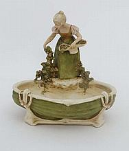 A Royal Dux Bohemia porcelain figural dish modelled as a girl collecting flowers beside a pool . Number 1652. With pink