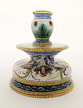 An Italian faience Ginori / Maiolica shaped candlestick, decorated with grotesque winged figures with scrolled detail to