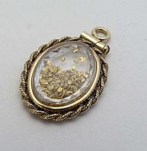 A gold and gilt metal pendant with glazed central section containing small gold nuggets . The whole 31/4