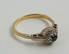An 18ct gold ring set with central sapphire bordered by diamonds in a platinum setting   Please Note -  we do not ma