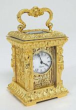 Carriage Clock :  A miniature ormolou cased clock ( timepiece ) , with two bevelled glass windows, t