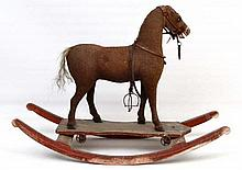 An Edwardian child's Pull along Horse mounted on a rocking base. Carved wooden frame with brown clot