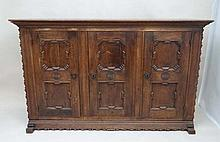 An early 20thC German oak 3 door cupboard with geometric like framed panelling, the doors opening to