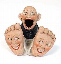 A 1920s  bisque china hat pin holder modelled as an open mouthed comic man with feet decorated with