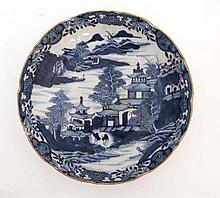 An oriental style blue and white dish. Depicting figures in an oriental landscape with pagodas and m