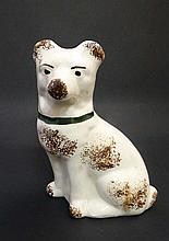 A 19thC small pottery figure of a seated dog decorated in brown with collar and sponged detail to bo