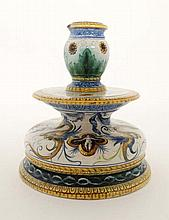 An Italian faience Ginori / Maiolica shaped candlestick, decorated with grotesque winged figures wit