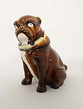 A pottery novelty tobacco pot and cover in the form of a brown glazed seated Bulldog wearing a yello