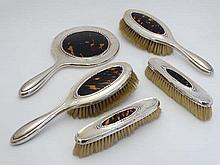 A 5-piece silver dressing table set comprising hand mirror and 4 brushes (2+2) all with inset tortoi