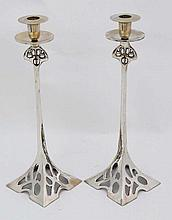 A pair of early 20 thC silver plated cast brass and pierced candlesticks with square bases, drip pan