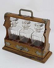 A Victorian oak 3 bottle Tantalus fitted with 3 glass bottles and stoppers and having central lock a