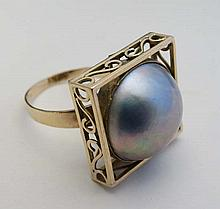 A 14ct gold dress ring set with a large pearl within a squared setting with scrolled frame