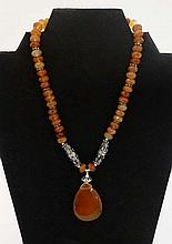 A silver necklace set with facet cut agate beads , ornate white metal beads and agate drop.