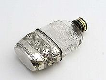 A cut glass hip flask with silver plate top and