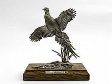 A pewter model of a a flighting pheasant on a