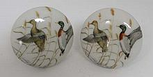 A pair of porcelain door knobs each depicting pair