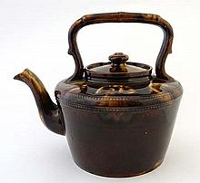A c1900 treacle glazed pottery kettle having