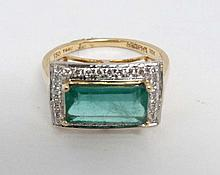 An 18ct gold ring set with central emerald bordere