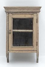 An early 20thC limed oak glazed fronted hanging wall cabine