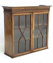 A 19thC mahogany astral glazed wall hanging cabinet with three shelves and blind fret carving to top 24 1/4
