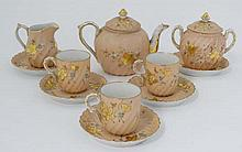 A late 19thC Tettau coffee service. Decorated in gilt with floral and foliate motifs on a salmon ground. Comprising of teapot, milk jug, sugar pot, 3 cups and 5 saucers. Green factory stamps to bases. The teapot 4 1/4'' High.