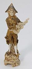 A Royal Dux Bohemia porcelain figure of a minstrel: modelled in tricorn hat, frock coat and breeches playing a guitar, on a rustic circular base, under shot ivory colours, applied pink triangle and impressed 332, 8 3/4'' High
