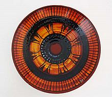 A Poole Pottery Delphis plate. Shape number 4 . Decorated by Patricia Wells. Decorated in black, red, orange and yellow, with an abstract circular design. Black printed dolphin mark to back. 10 1/2'' diameter