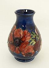 A small Moorcroft Pottery vase in ' Anemone '  pattern on a dark blue ground. Mid 20th C.  Marked WM to base together with impressed factory marks. 5 1/4'' High.