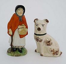 A Victorian Staffordshire figure depicting an elderly female wearing red cloak, tied bonnet and holding a cane, and standing on a grassy circular base. Indistinct stylised XS marks to base. Height 7