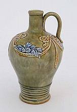 A  Royal Doulton stoneware single handled amphora / vase. The Green background having ridged relief detail to base and blue floral and foliate detail with brown bows to top.  Number 7546. 8'' High