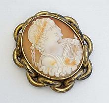 A Cameo brooch depicting 2 classical figures with a harp wi